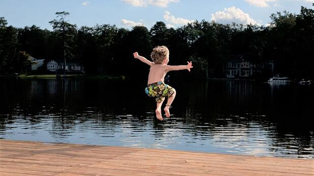Boy jumping in lake istock